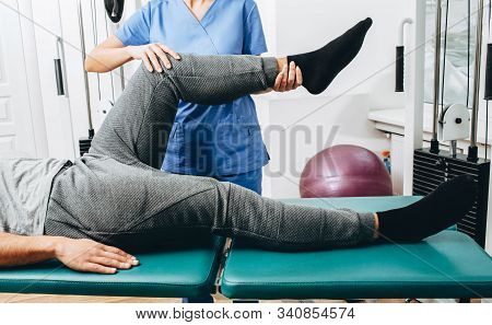 Joint, Knee And Leg Pain Treatment. Physiotherapist Doing Treatment Exercise Patients Knee Close-up