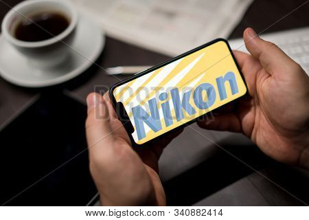 New York, New York / USA - 11 11 2019: Logo of Nikon on the iPhone X in hands in office