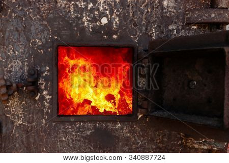 Open door with fire in a old Thai traditional crematorium.