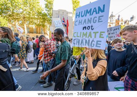 LONDON - SEPTEMBER 20, 2019: Climate Change protester carrying a homemade protest placard past The Cenotaph on Whitehall, London at an Extinction Rebellion march