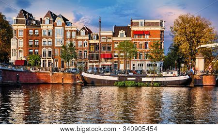 Amsterdam, Netherlands. Floating House and houseboat at channels by banks. Traditional dutch dancing houses among trees. Evening autumn street above water pink sunset sky with clouds.