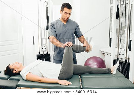 Woman Treatment Her Joint With Therapist. Physical Therapist Helping His Patient Doing Exercise For
