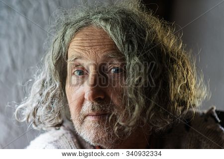 Portrait Of A Senior Man With Curly Hair.