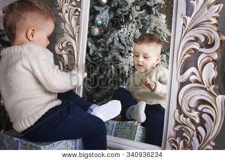 Little Boy Sitting On The Present Box In Front Of The Tracery Mirror Near The Christmas Tree