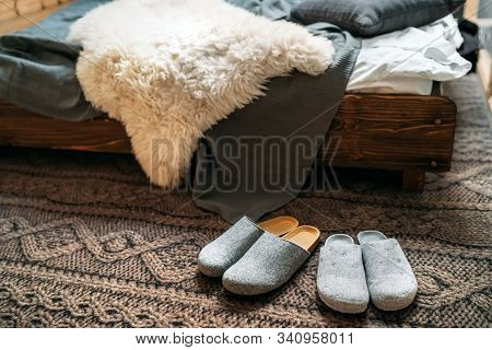 The Two Pair Of Gray Home Slippers Near The Wooden Bed On The