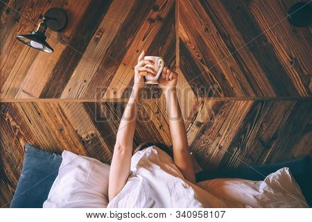 Lazy Female Lying Under The White Blanket On The  Linen Bed And Holding The Fresh Coffee Cup In The