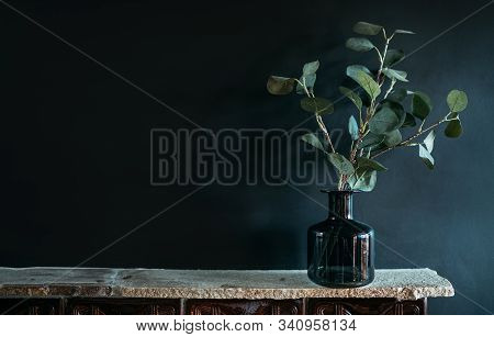 Green Tree Branch Putted Into Black Glass Vase On The Natural Stone Mantel Shelf On The Black Color