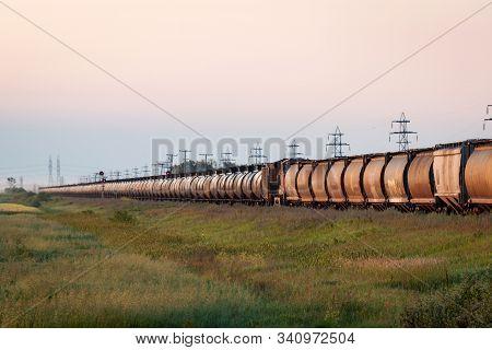 Dawn Train Of Grain Cars And Tank Cars Across The Prairie