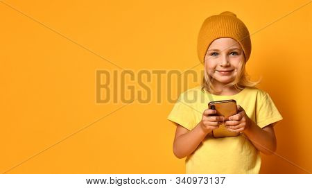Little Blonde Girl Dressed In T-shirt And Hat, Holding Mobile Phone, Looking At You With Joyful Smil