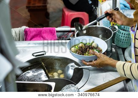 Cooker Making Thai Noodle Of Jumbo Beef Ball With Meaty Sell On Cart At Night. Thai Street Food. Tha