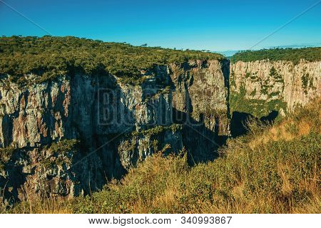 Itaimbezinho Canyon With Steep Rocky Cliffs Going Through A Flat Plateau Near Cambara Do Sul. A Smal