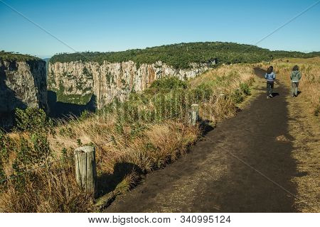 Dirt Pathway And People At The Itaimbezinho Canyon With Steep Rocky Cliffs In A Flat Plateau Near Ca
