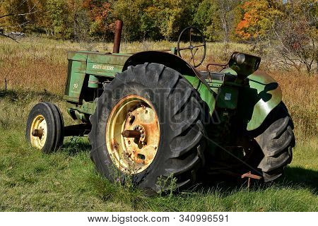 Vergas, Minnesota, October 6, 2019: The Old 70 John Deere Tractor Against Autumn Leaves Is A Product