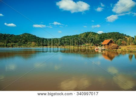 Small Rustic Shack Reflected On The Lake Of Crystal Clear Water And Hills Covered By Grove Near Camb