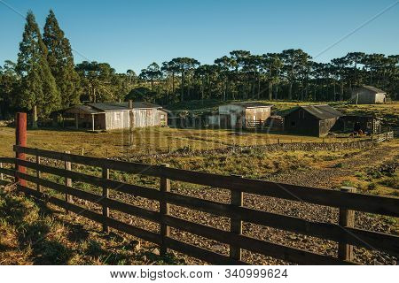 Shabby Shacks From A Ranch With Wooden Fence On Lowland Covered By Dry Bushes And Trees Near Cambara