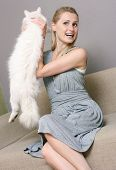 happy woman holding cat while sitting in couch poster