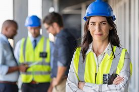 Portrait of woman engineer at building site looking at camera with copy space. Mature construction manager standing in yellow safety vest and blue hardhat with crossed arms. Successful architect.