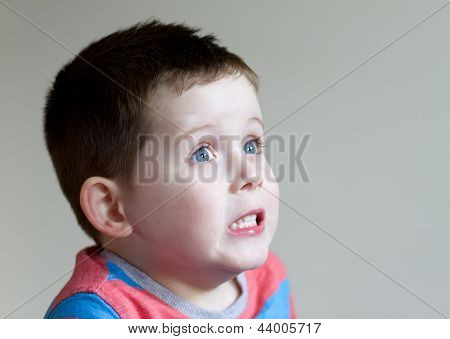 Little Boy Pulling A Frightened Expression