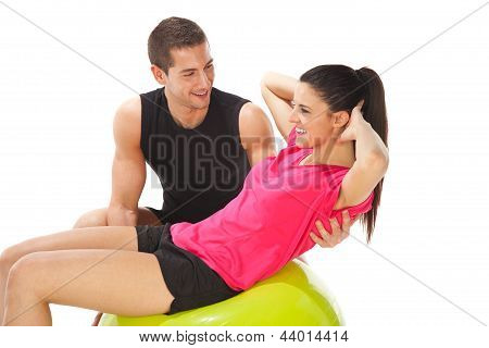 Woman With Her Personal Trainer Doing Exercises On Fitness Ball