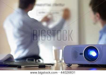 Business conference or lecture with businessman writing on whiteboard and lcd projector in foreground poster