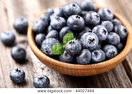 Ripe blueberry in a wooden plate