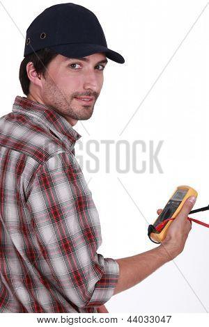 Tradesman holding a multimeter