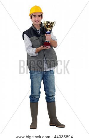 Happy construction worker holding golden cup