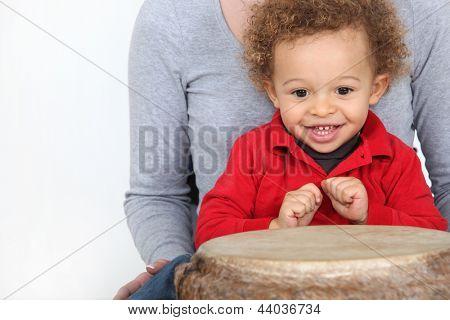 Little boy sat by bongo drum