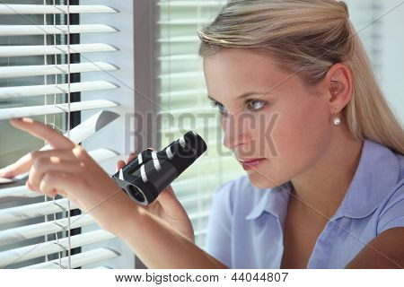 Office worker looking out of a window with binoculars