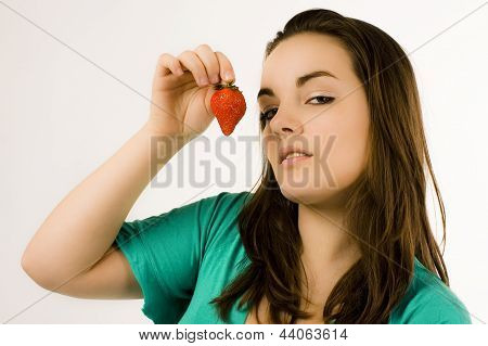 Beautiful young woman showing strawberry