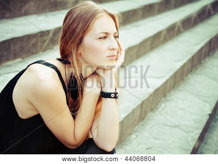 Portrait Of The Beautiful Blond Woman On The Stairs