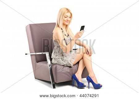 Young woman typing a text message on a mobile phone and sitting in an armchair, isolated on white background