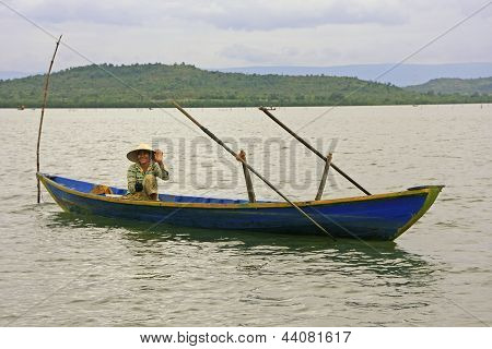 REAM, CAMBODIA-DECEMBER 9: An unidentified woman fishes from a boat on December 9, 2011 in Ream Nati