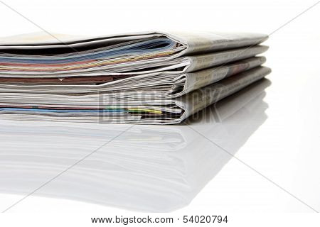 several newspapers journals stacked on white background poster