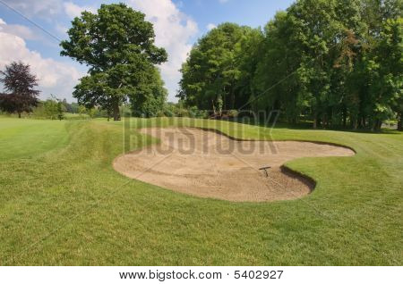 golf sand bunker in scenic location trees and blue sky clouds