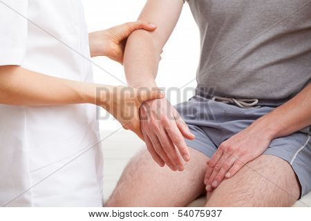 Orthopaedist examining injured arm of man in middle age poster