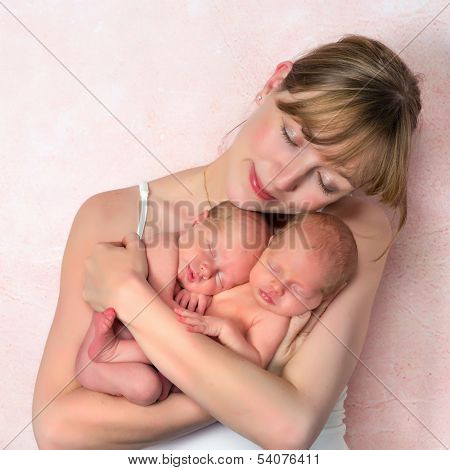 Beautiful young mother holding her ten days old newborn twin baby girls