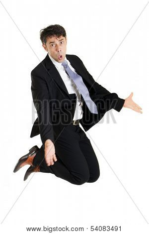 Businessman making an imploring impassioned gesture with outstretched arms while either kneeling on the floor or leaping in the air with his knees bent, isolated on white