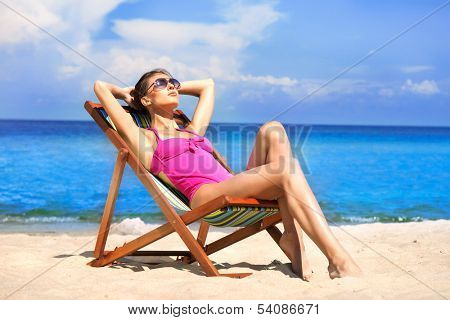 A young woman in a swimsuit relaxing on a deckchair on the beach