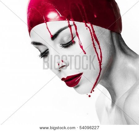 Dramatic artistic portrait of a bleeding woman with closed eyes and a serene expression wearing a red cap dripping blood with selective colour to the cap, blood and her red lips, isolated on white