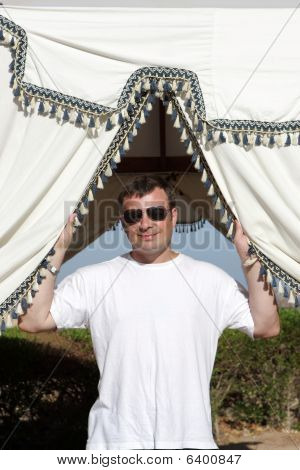 Man Poses In Summerhouse