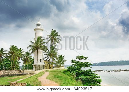 Lighthouse and palm trees on background sky.