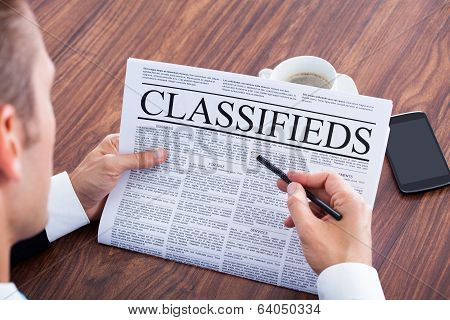 Close-up Of Young Businessman Reading Classifieds