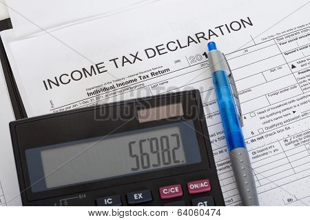 Closeup of income tax declaration calculator and pen poster