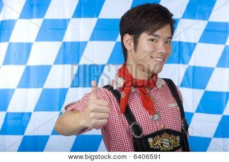 Junge mit bayerischen Oktoberfest Lederhosen (Lederhose) zeigen Daumen