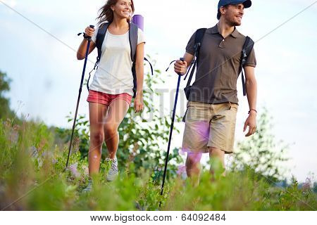 Portrait of happy couple hiking in the countryside at summer