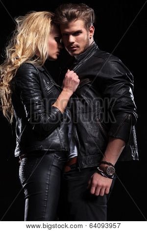 photo of a young man looking into the camera while holding his girlfriend which is pulling his collar . on black background