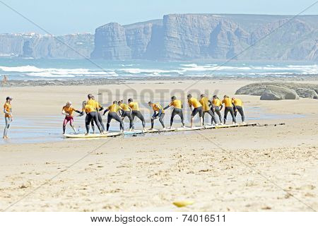VALE FIGUEIRAS, PORTUGAL - August 29 2014:  Surfers doing excersises on the famous surfers beach Vale Figueiras in Portugal