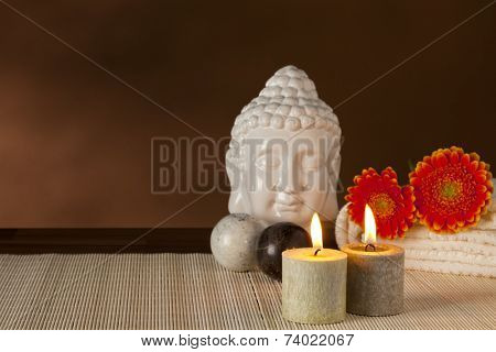 Spa still-life with buddha head, Qigong balls, candles and flowers