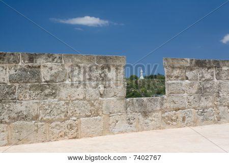 Christ Statue View Across A Castle Battlement